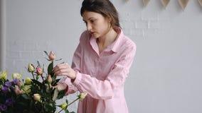 Berufsflorist, der Rosen im Blumenladen vereinbart lizenzfreies stockbild