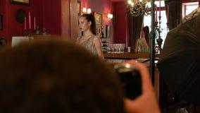 Berufsfotograf macht eine Fotosession von einem jungen Modell im Retrostil Modeindustrie, Sch?nheit, B?hne hinter dem Vorhang stock video footage