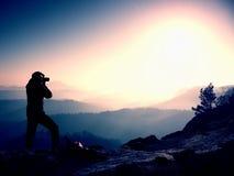 Berufsfotograf macht Fotos mit Spiegelkamera auf Spitze des Felsens Träumerische Fogylandschaft, entspringen orange rosa nebelhaf Stockfotos