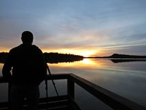 Berufsfotograf Silhouette mit Stativ während des Sonnenuntergangs über schönem See mit bewölktem Himmel im Hintergrund lizenzfreies stockfoto