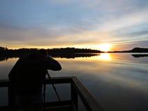 Berufsfotograf Silhouette mit Stativ während des Sonnenuntergangs über schönem See mit bewölktem Himmel im Hintergrund stockbild