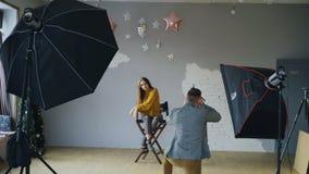 Berufsfotografmann, der Foto des schönen vorbildlichen Mädchens mit Digitalkamera im Studio macht Lizenzfreies Stockfoto