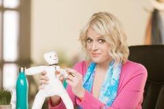 Berufsfrau, die eine Wodu-Puppe stößt Lizenzfreies Stockbild