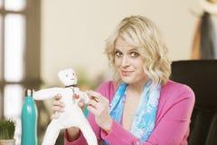 Berufsfrau, die eine Wodu-Puppe stößt stockfoto