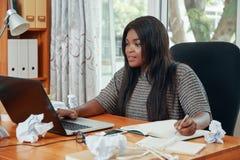 Berufsfrau, die mit Laptop und Notizblock arbeitet lizenzfreies stockbild