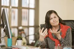 Berufsfrau, die zum Telefon-Inhalt reagiert Stockbilder