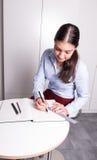 Berufsfrau zeichnet in ein Notizbuch mit Machthaber und penc Lizenzfreies Stockbild