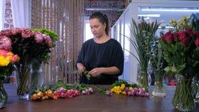 Berufsfrauen-Floristenschnitte stiegen Dornen über der Tabelle im Blumenladen stock video footage