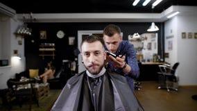Berufsfriseur, der dem stilvollen männlichen Kunden Haarschnitt sitzt im Friseursalon macht stock footage