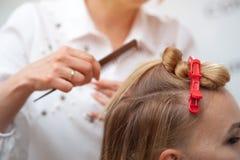 Berufsfriseur, der eine Frisur zu einem blonden Modell macht stockfotos
