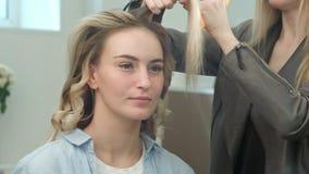 Berufsfriseur, der Frisur des schönen blonden Modells und sie lächelnd tut stockfotografie