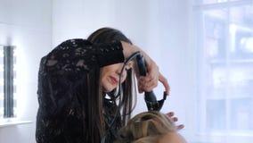 Berufsfriseur, der Frisur für Frau tut - die Herstellung kräuselt sich stock video
