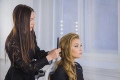 Berufsfriseur, der Frisur für junge hübsche Frau mit dem langen Haar tut Lizenzfreie Stockbilder