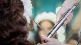 Berufsfriseur, der gelocktes Haar für Brunettemodell herstellt lizenzfreies stockbild