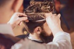 Berufsfriseur, der Haar seines Kunden anredet Stockfoto