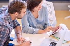 Berufsgeschäftsfrau, die ihrem männlichen Partner Finanzzahlen auf Tablette zeigt Stockfoto