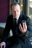 Berufsgeschäftsmann, der entlang des Handys anstarrt Lizenzfreie Stockfotografie