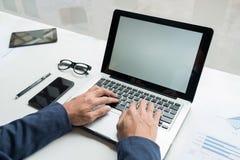 Berufsgeschäftsmann, der in seinem Büro mit Laptop und s arbeitet Lizenzfreie Stockfotografie
