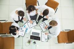 Berufsgeschäftsteam, das eine neue Finanzstrategie der Firma an einem Arbeitsstandort in einem modernen Büro entwickelt Lizenzfreies Stockbild