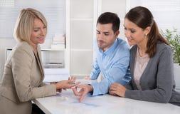 Berufsgeschäftstreffen: junge Paare als Kunden und Lizenzfreies Stockbild