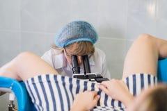 Berufsgynäkologe, der ihren weiblichen Patienten auf einem gynäkologischen Stuhl überprüft stockfotos