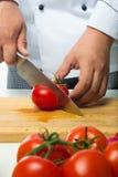 Berufshände hackten Tomaten auf einem hölzernen Brett Stockfoto