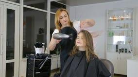 Berufshaaraufbereiter trocknet Haar des jugendlich netten Mädchens stock video