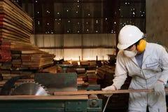 Berufsjunger arbeitnehmer in der weißen Uniform und in der Schutzausrüstung, die ein Stück Holz auf Tabelle schneidet, sah Maschi Stockfoto