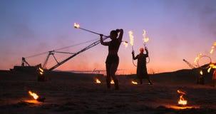 Berufskünstler zeigen eine Feuershow an einem Sommerfestival auf dem Sand in der Zeitlupe Vierte Personenakrobaten von stock video footage