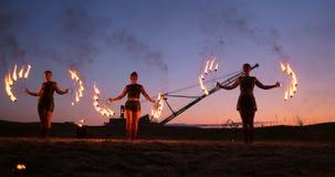 Berufskünstler zeigen eine Feuershow an einem Sommerfestival auf dem Sand in der Zeitlupe Vierte Personenakrobaten von stock footage