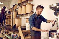 Berufskaffeeröster, der eine Bratmaschine im dist betreibt Stockbild