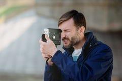Berufskameramann des bärtigen Mannes beobachtet und schießt 8mm MO Stockfotos