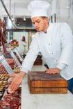 Berufskoch, der frisch warmes Gericht schnüffelt lizenzfreie stockfotografie