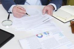 Berufskopfjäger, der Zusammenfassung am Schreibtisch wiederholt und Entscheidung trifft, bevor Angestellter eingestellt wird stockfoto