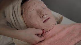 Berufskosmetiker entfernt die Maske vom Gesicht eines jungen Mädchens Neues Konzept im Cosmetology stock video footage