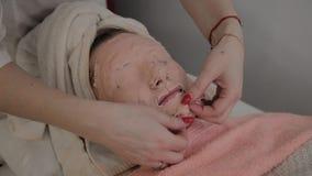 Berufskosmetiker entfernt die Maske vom Gesicht eines jungen Mädchens Neues Konzept im Cosmetology stock footage