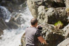 Berufslandschaftsphotograph, der einen Wasserfall schie?t lizenzfreie stockfotos