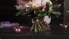 Berufsmädchenflorist bindet die Unterseite des Blumenstraußes mit silk rosa Bändern Dunkles Studio Langsame Bewegung stock video