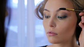 Berufsmake-upkünstler, der Augenbrauen des Kunden kämmt Lizenzfreies Stockbild