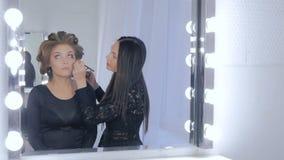 Berufsmake-upkünstler, der Eyeliner um das gesamte Auge des Modells anwendet stock video