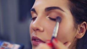 Berufsmake-upkünstler, der Lidschatten am vorbildlichen Auge unter Verwendung der speziellen Bürste anwendet Schönheits-, Make-up stock video footage
