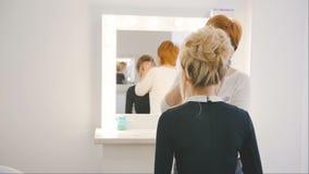 Berufsmake-upkünstler, der Make-up auf dem Gesicht des schönen jungen sinnlichen Modells mit dem blonden langen Haar anwendet stock footage