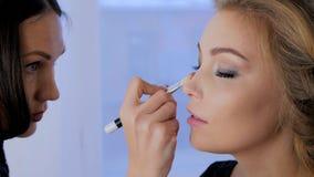 Berufsmake-upkünstler, der Make-up auf Frau ` s Gesicht anwendet Stockbilder