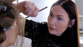 Berufsmake-upkünstler, der Make-up auf Frau ` s Gesicht anwendet Stockbild