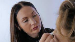 Berufsmake-upkünstler, der Make-up auf Frau ` s Gesicht anwendet stock video footage