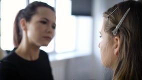 Berufsmake-upkünstler in der Modeindustrie tut junges Modell des Makes-up, das auf einem Stuhl in ihrer Schönheit sitzt stock footage