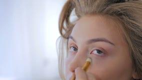 Berufsmake-upkünstler, der niedrige Lidschattensahnezündkapsel am vorbildlichen Auge anwendet stock video