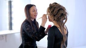 Berufsmake-upkünstler, der Pulver am Frauengesicht anwendet Lizenzfreie Stockfotografie