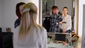 Berufsmake-upkünstler, die mit einer Bürste arbeiten anerkannter Stilist und der Kunde im Spiegel stock footage