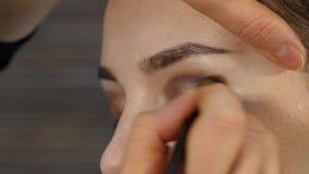 Berufsmake-upkünstler macht Augenmake-up auf einem Kundengesicht Schönheitsmodeindustrie stock video footage